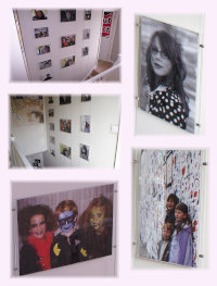 Wire suspended poster holders displaying family photos in home stairway